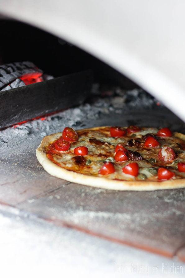 pizza met tomaatjes, zongedroogde tomaat en kappertjes