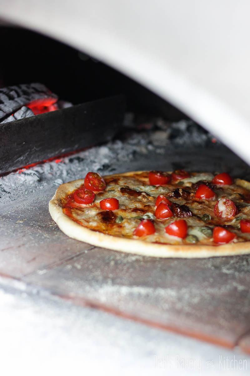 Pizza met tomaat, zongedroogde tomaat en kappertjes